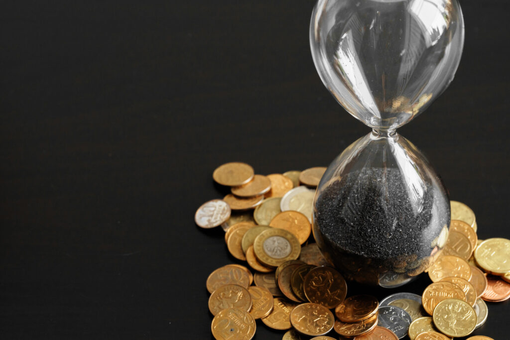 Time is money. Close up of hourglass with money coins